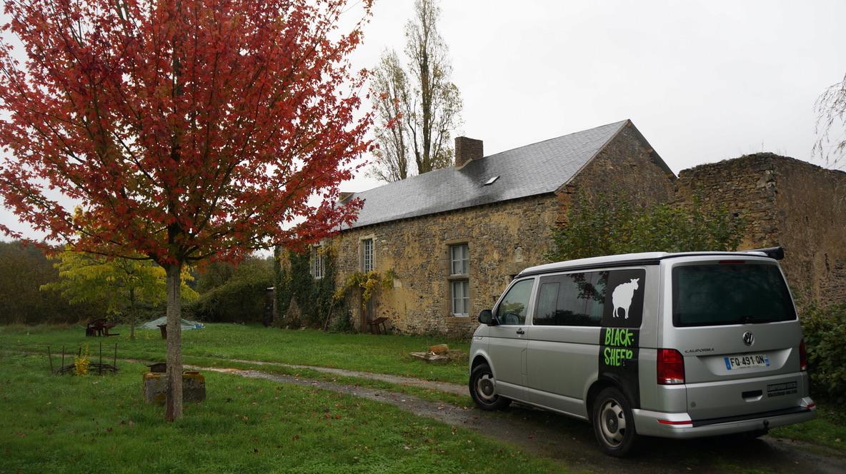 van devant maison en pierre et arbre aux feuilles rouges