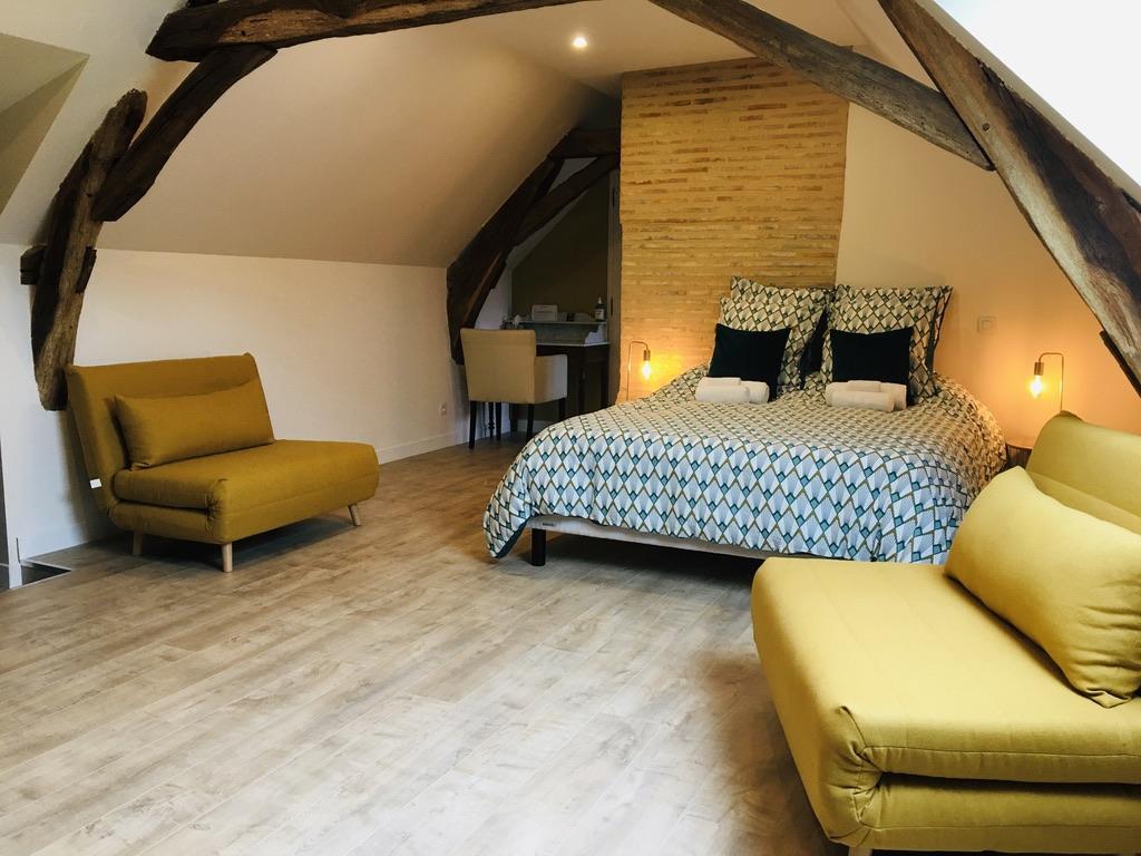 chambre lit double et 2 chauffeuses jaunes poutre en bois