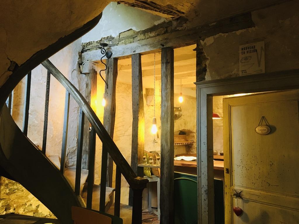 escalier premier plan et cuisine ancienne en second plan