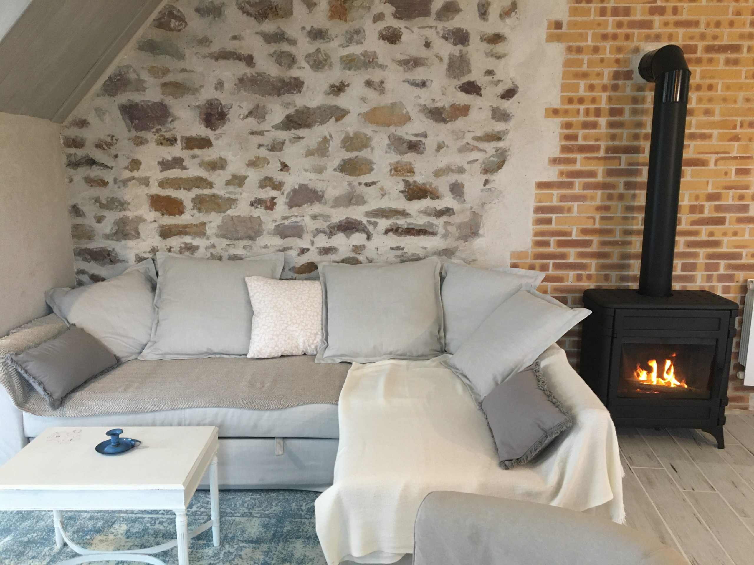canapé et poêle allumé sur mur en pierre et brique