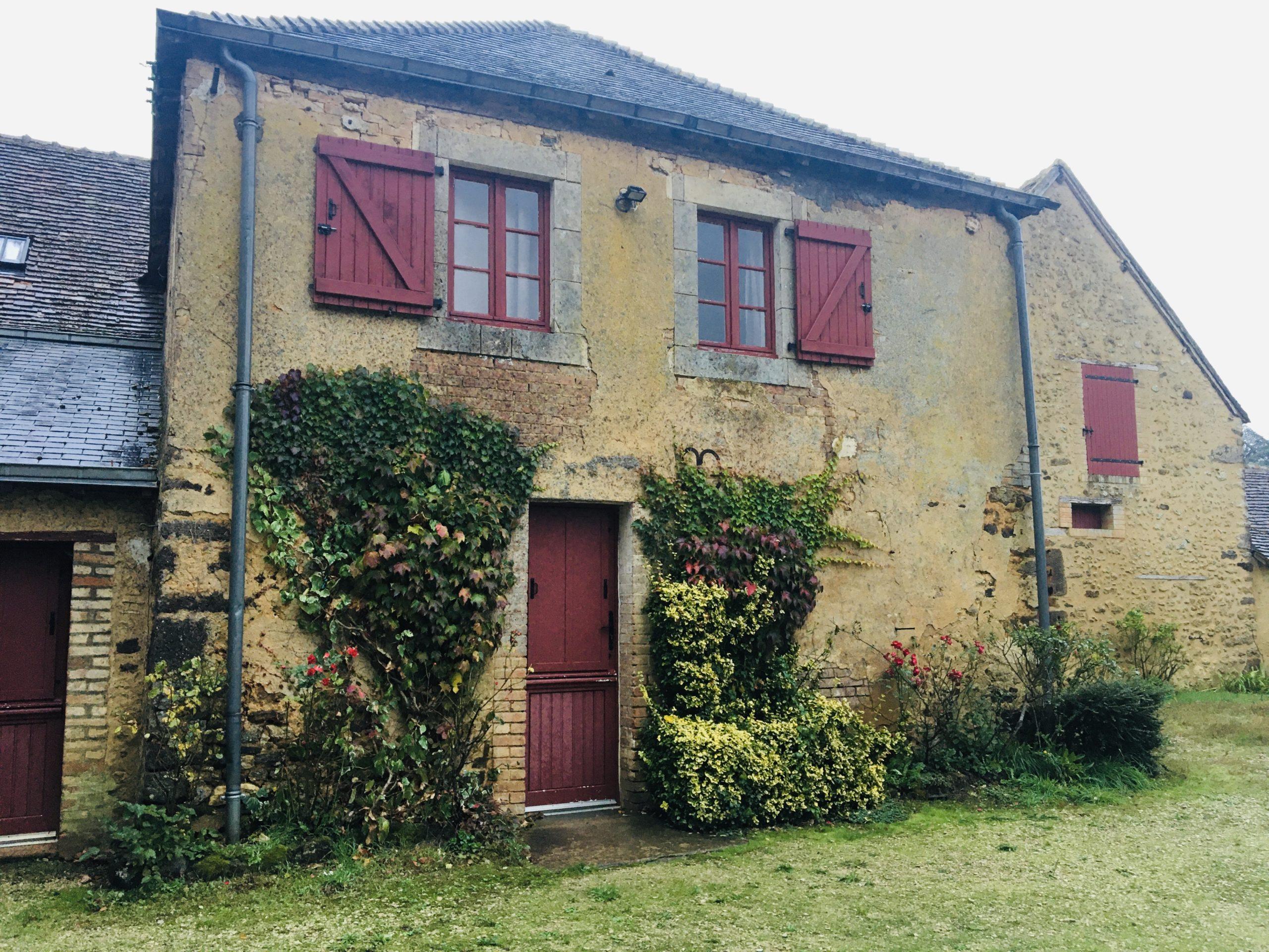 façade vieille maison volets rouges